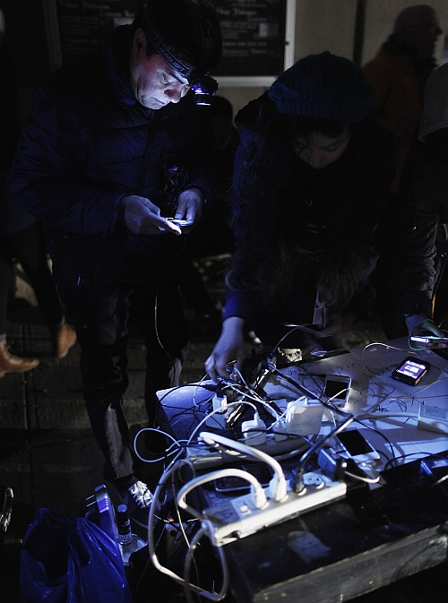 People charge their cell phones at a generator supplied by a local theatre troupe in the Lower East Village, in the aftermath of Hurricane Sandy in New York