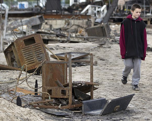 A boy walks among devastated homes affected by fire and Hurricane Sandy in the Breezy Point section of the Queens borough of New York