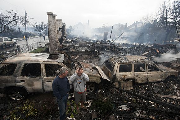 Residents look over the remains of burned homes in the Rockaways section of New York