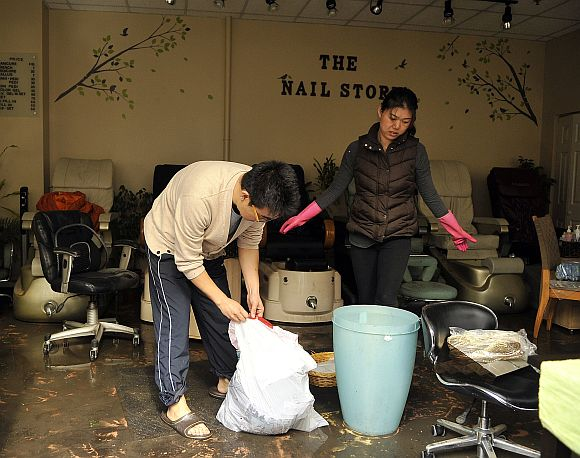 Jimmy Lee (L), owner of The Nail Store begins the cleanup of his shop from the damage done from Hurricane Sandy in Hoboken, New Jersey