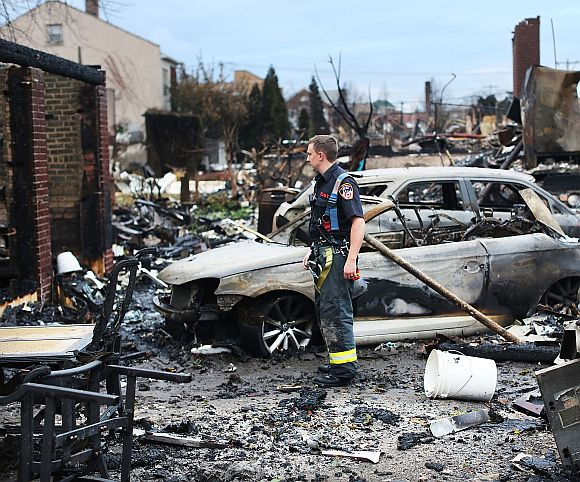 A firefighter stands among the remains of homes burned down in the Rockaway neighbourhood during Hurricane Sandy in the Queens borough of New York City