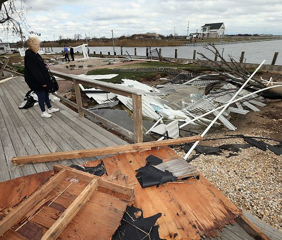 Resident Pat Lore checks out the damage caused to her home from Hurricane Sandy on the Western Concourse in Amity Harbor, New York