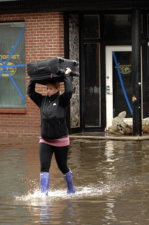 Resident Dana Szymanski carries her luggage over her head as she evacuates after Hurricane Sandy in Hoboken, New Jersey