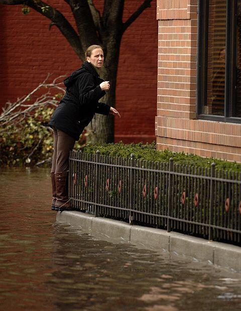 A woman stands on a curb as a street remains flooded from Hurricane Sandy in Hoboken, New Jersey