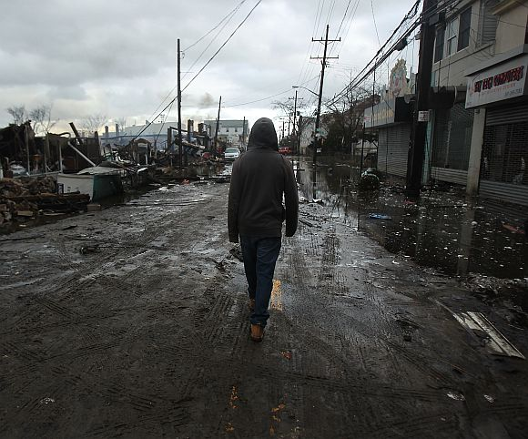 A person walks by homes and businesses destroyed during Hurricane Sandy in the Rockaway section of the Queens borough of New York City