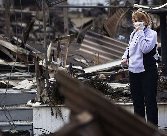 A woman stands outside the wreckage of homes devastated by fire and the affects of Hurricane Sandy in the Breezy Point section of the Queens borough of New York