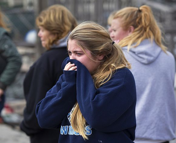 A girl cries after looking through the wreckage of homes devastated by fire and the affects of Hurricane Sandy in the Breezy Point section of the Queens borough of New York