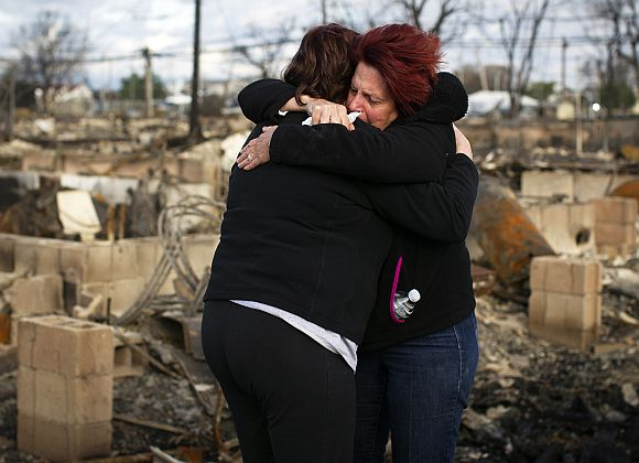 Neighbours Lucille Dwyer and Linda Strong embrace after looking through the wreckage of their homes devastated by fire and the effects of Hurricane Sandy in the Breezy Point section of the Queens borough of New York