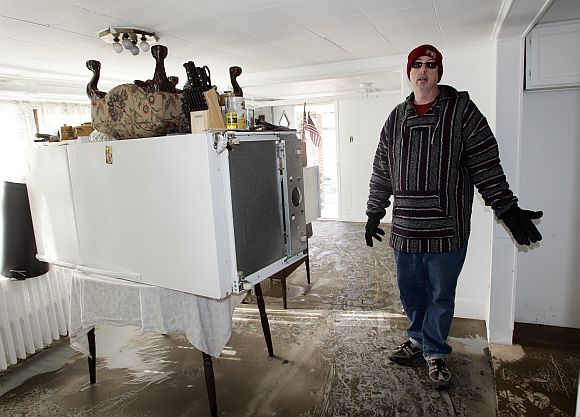 Robert Lukasiewicz stands next to a refrigerator placed on a table as he describes how 20 inches of water flooded the ground floor of his home at Iowa and Baltic Avenues in Atlantic City, New Jersey