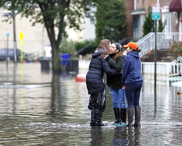 People greet each other in the street as they make their way out of the floodwaters in Hoboken, New Jersey