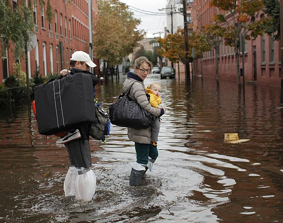 A family walks through a flooded street at Hoboken in New Jersey