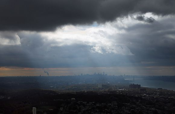 Rays of sunshine stream through the clouds with the Manhattan skyline