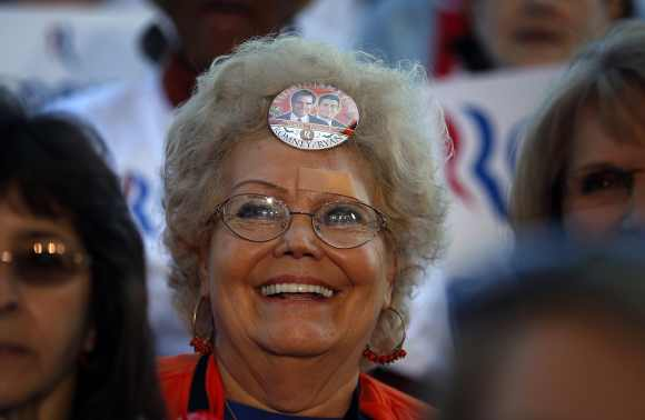 An audience member with a campaign button in her hair waits for Republican presidential nominee Mitt Romney at a campaign rally in Tampa, Florida