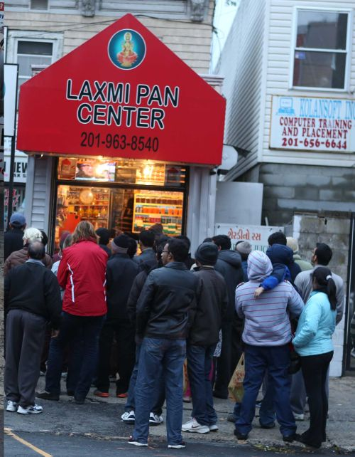 Indian Americans gather outside Laxmi Pan Center in Jersey City on Wednesday