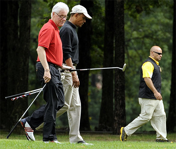Obama walks the fairway with Clinton as they play golf at Andrews Air Force Base