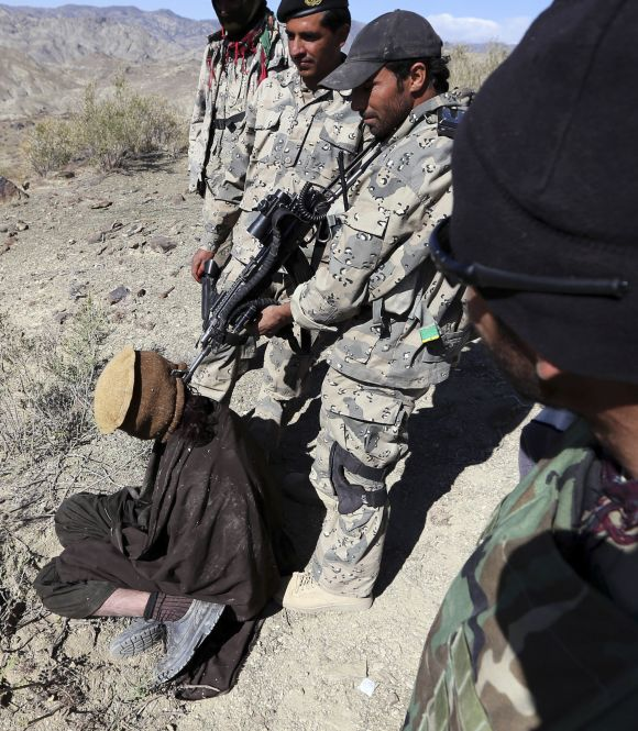 Afghan border policemen with a detained suspected Taliban fighter near the town of Walli Was in Paktika province, near the border with Pakistan.