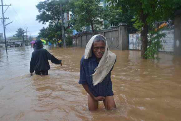 A man wades through knee-deep water in Vizag