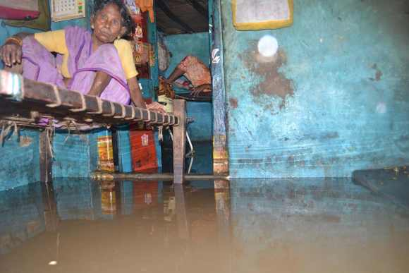 A old woman sits in her flooded house in an Andhra village