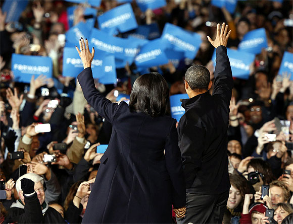 US President Barack Obama and First Lady Michelle Obama wave to their supporters