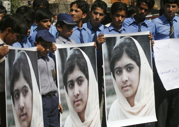 Students hold pictures of Malala Yousufzai to show their solidarity at a school in Karachi