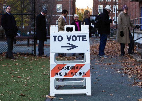 People wait in line to vote during the US presidential election in Cambridge, Massachus