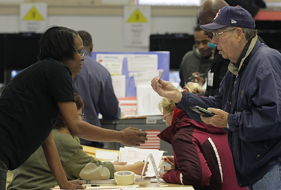 A man presents his voter ID card to a poll worker to vote in the U.S. residential election at a displaced polling center in the Coney Island section of Brooklyn, New York
