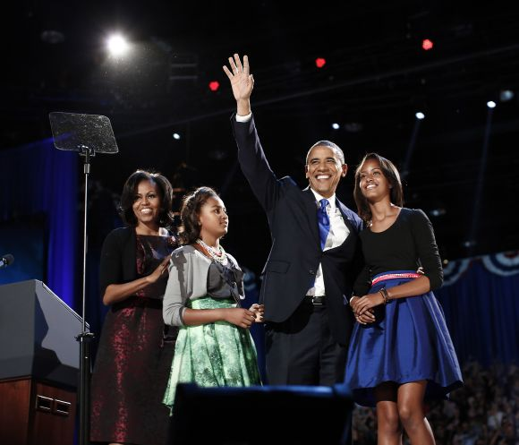 US President Barack Obama gathers with his wife Michelle Obama and daughters Sasha and Malia during his election night victory rally in Chicago