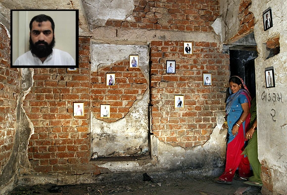 A survivor stands next to pictures of her fami