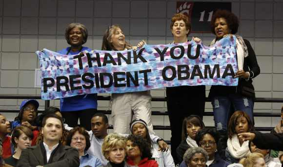 Supporters hold a sign as Obama speaks at a campaign event at Fifth Third Arena at the University of Cincinnati