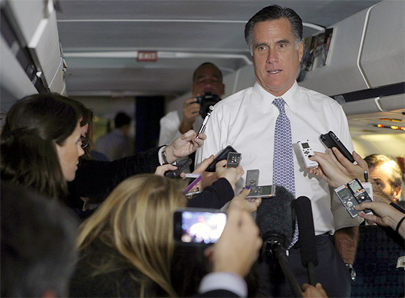 Republican presidential nominee Mitt Romney talks to reporters on his campaign plane