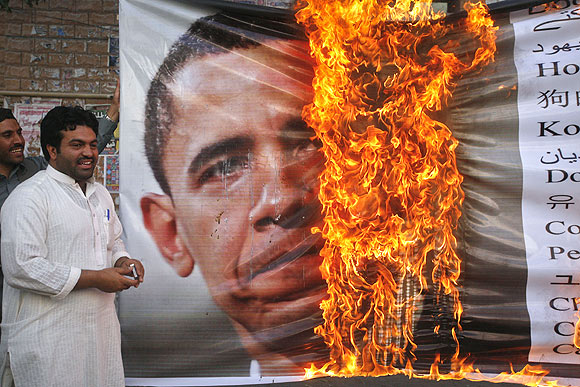 Supporters of Awami Majlis-e-Amal Pakistan stand next to a burning image of US President Barack Obama during an anti-American rally in Quetta