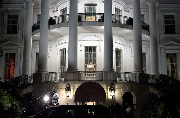 US President Barack Obama (silhouetted in car window) and his family return to the White House