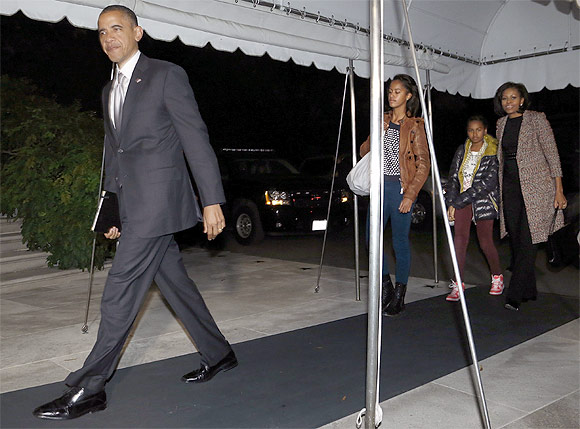 US President Barack Obama, his wife Michelle and their daughters Malia and Sasha return to the White House
