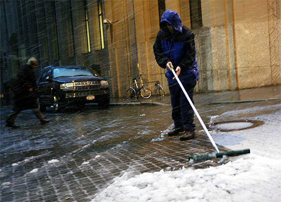 worker clears snow outside the New York Stock Exchange in New York