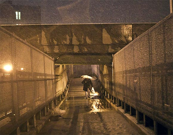 A man walks across an overpass during a nor'easter, also known as a northeaster storm, in the Red Hook Neighborhood of New York
