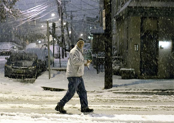 A man walks in the snow during the nor'easter, also known as a northeaster storm, in Jersey City, New Jersey
