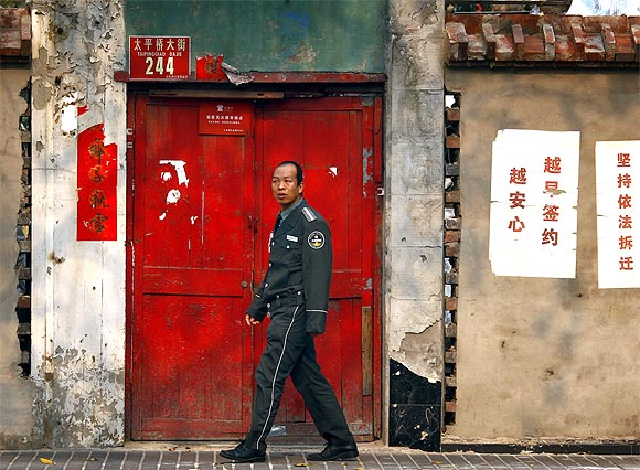 A security guard walks past eviction notices stuck to the exterior wall of a house before it is demolished in central Beijing