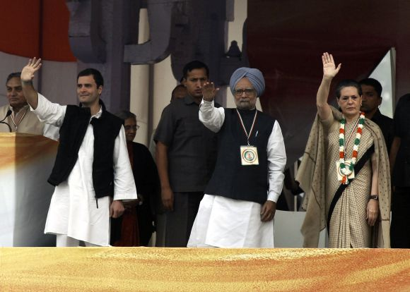 PM Singh, Sonia Gandhi and Rahul Gandhi wave to their supporters during rally in New Delhi's Ramlila Maidan ground on Sunday