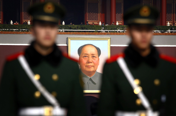 Paramilitary policemen stand guard in front of the giant portrait of former Chinese chairman Mao Zedong at Beijing's Tiananmen Square, as security is tightened around the square and the adjoining Great Hall of the People