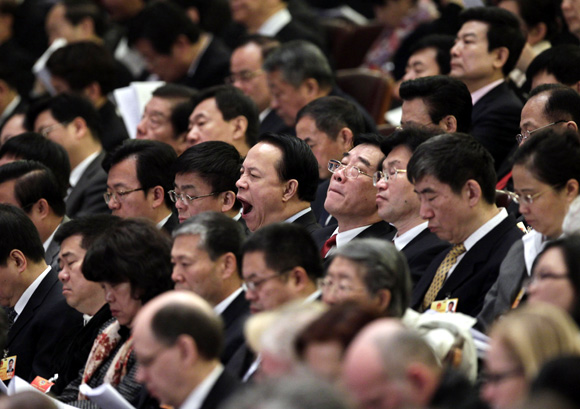 A delegate yawns during the opening ceremony of the National People's Congress at the Great Hall of the People in Beijing