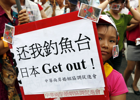 A girl holding a placard reading Give Diaoyutai back. Japan get out! takes part in an anti-Japan protest in Taipei