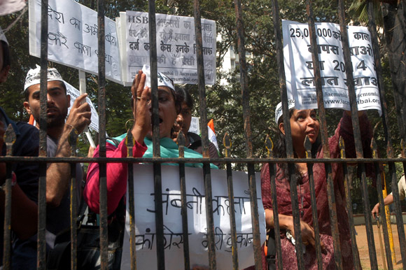 IAC actvists stand outside the Ambani residence and shout slogans