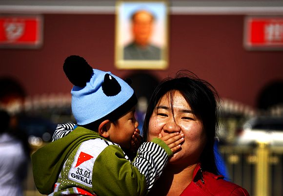 A boy and his mother pose for a photograph at Beijing's Tiananmen Square