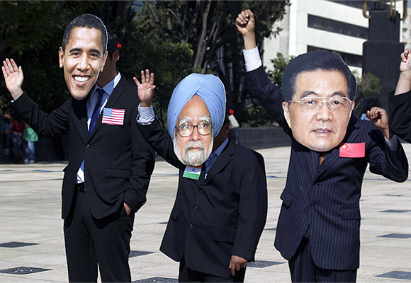 Activists wearing masks of Obama, Dr Singh and Chinese President Hu Jintao wave during a protest in Mexico