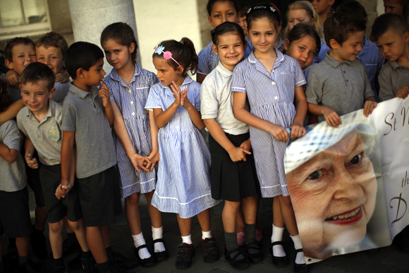 School children hold a banner with a picture of Queen Elizabeth II during her Diamond Jubilee celebrations