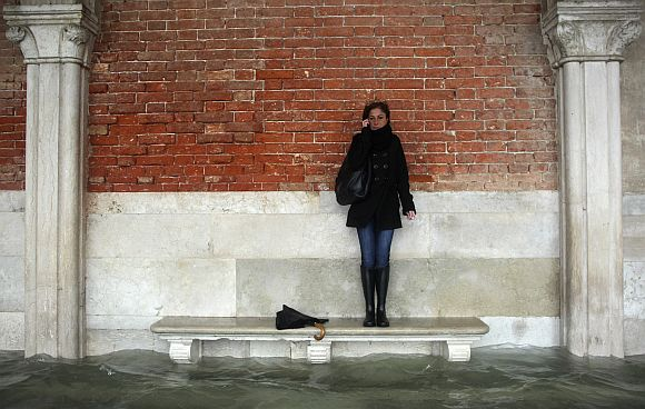 A woman stands on a bench above a flooded street during a period of seasonal high water in Venice