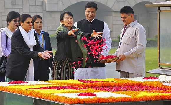 Aung San Suu Kyi scatters rose petals at the Mahatma Gandhi memorial at Rajghat in New Delhi on Wednesday
