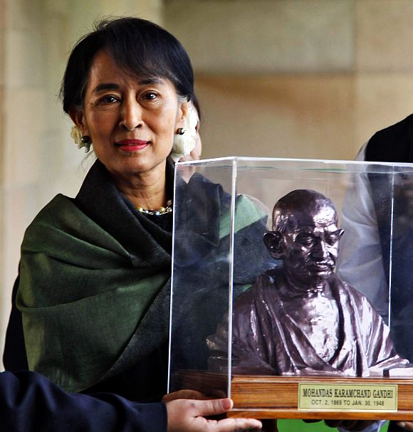 Suu Kyi holds a bust of Mahatma Gandhi at his memorial at Rajghat in New Delhi