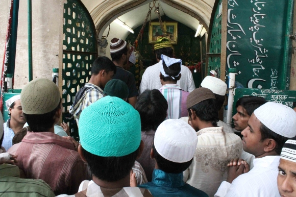 Members of the Muslim community pray at a shrine near Charminar