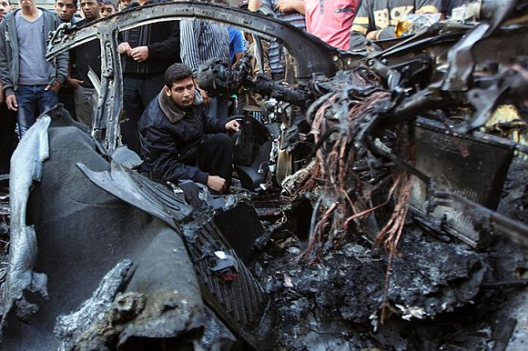A Hamas police officer checks the destroyed car